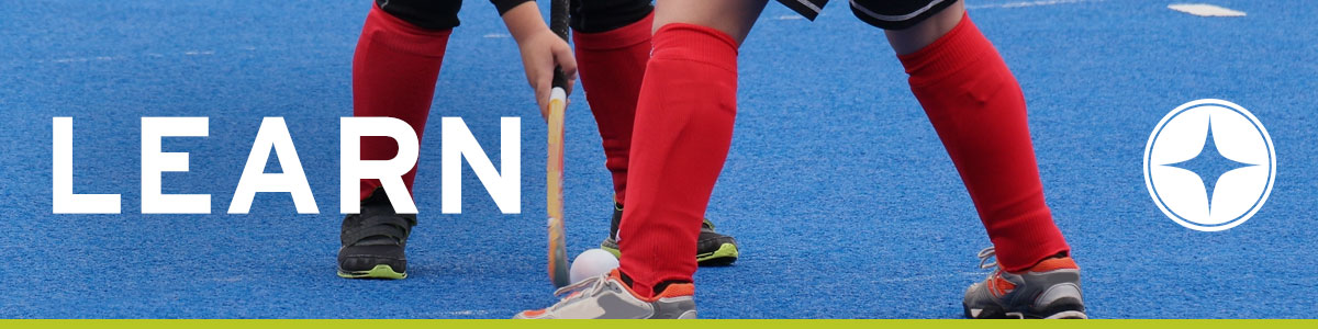 Image of two field hockey players with the word LEARN written over them.