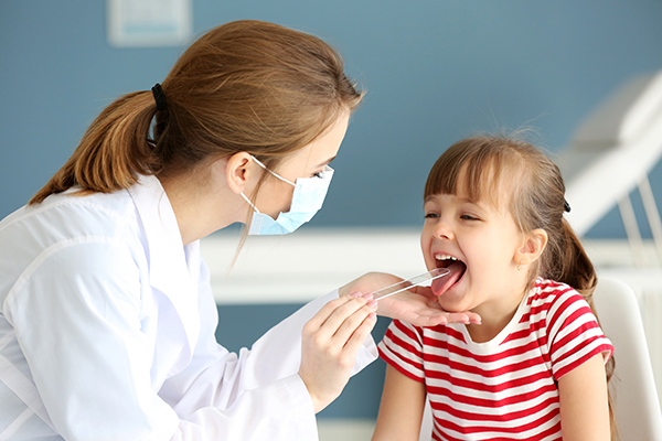 A female doctor putting a tongue depressor in a young patient's mouth.