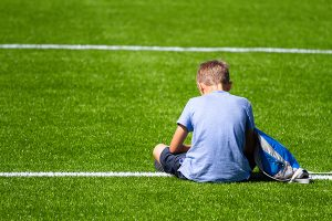 Young white boy sitting on soccer field alone, view from behind.