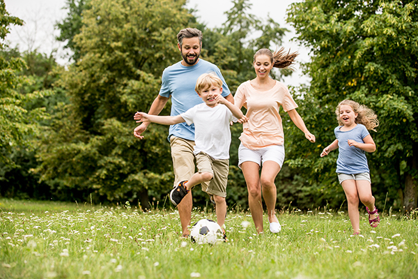 A white couple playing soccer outside with two children.