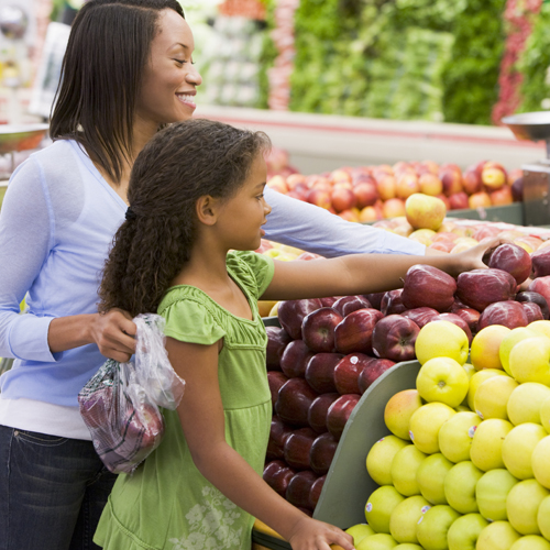 A black other and daughter picking out apples at a grocery store.