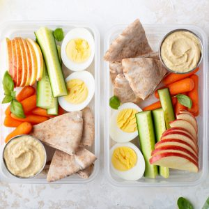 Hummus with veggies and fruit and hard boiled egg in plastic containers.