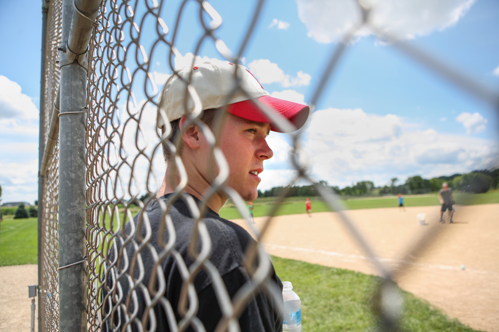 White male teen standing against fence during baseball game.