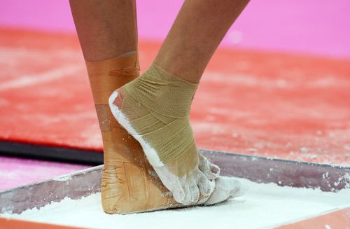 Close up of a female gymnasts feet in chalk.